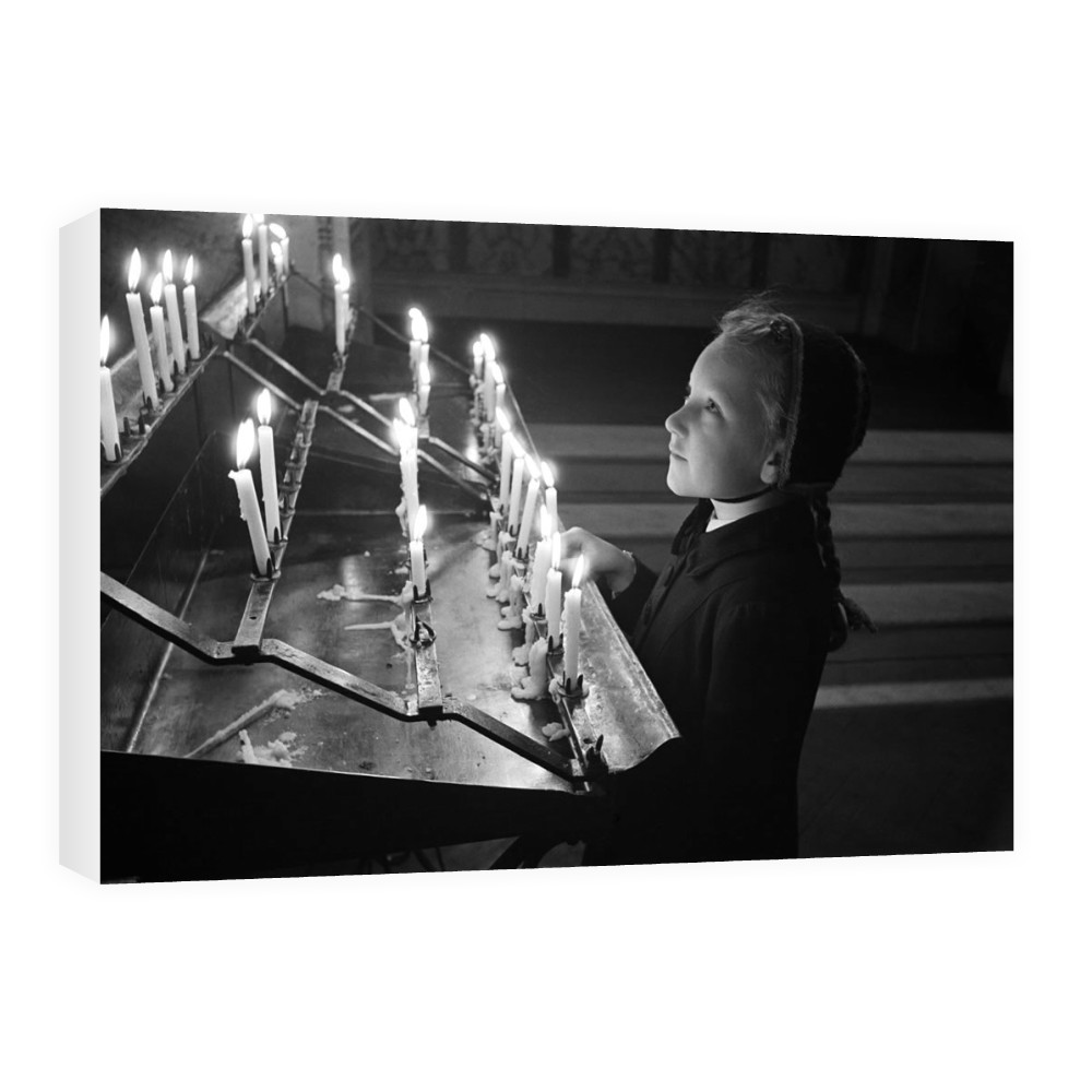 A young girl looking at candles at.. Canvas