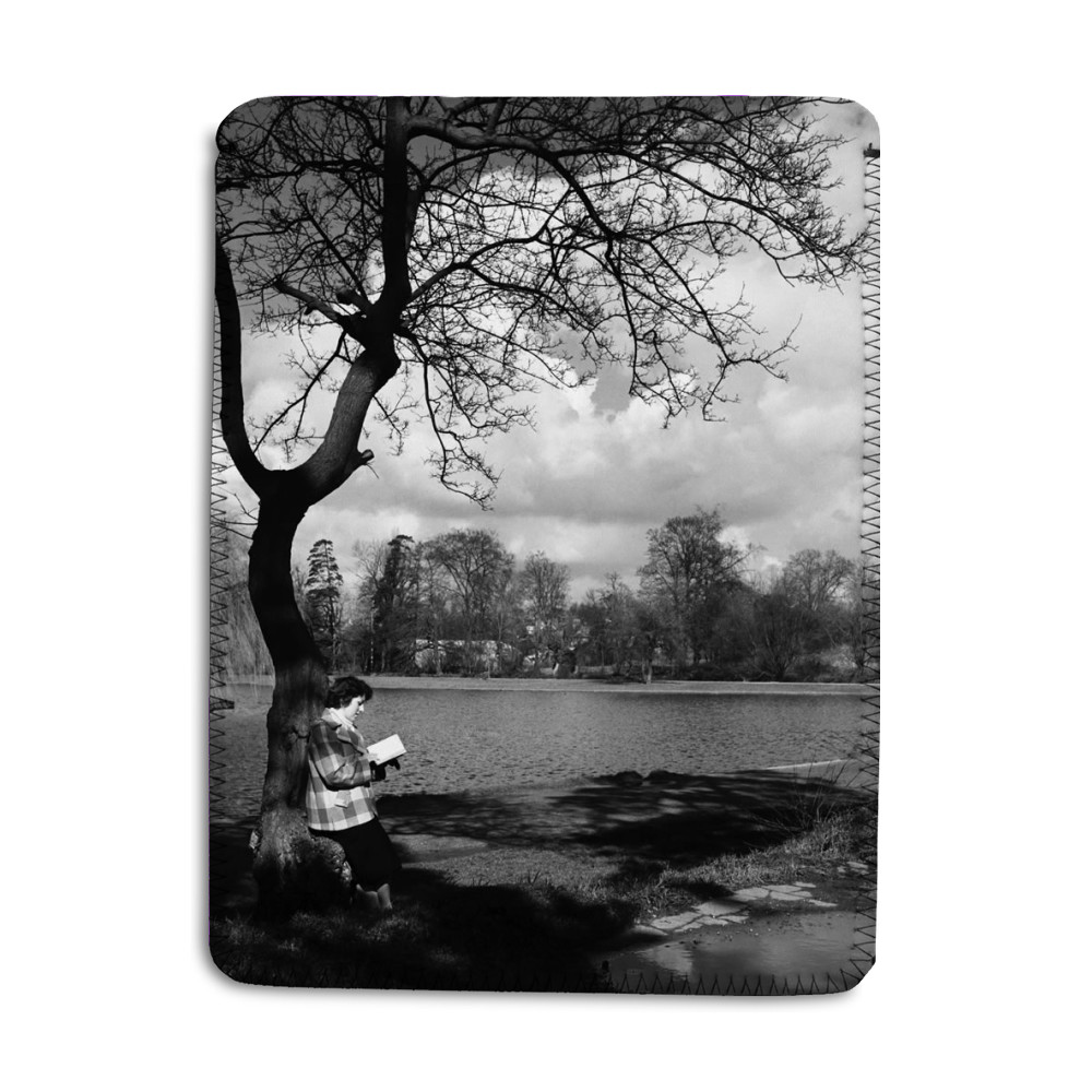 Woman reading her book by the lake in.. iPad Sleeve