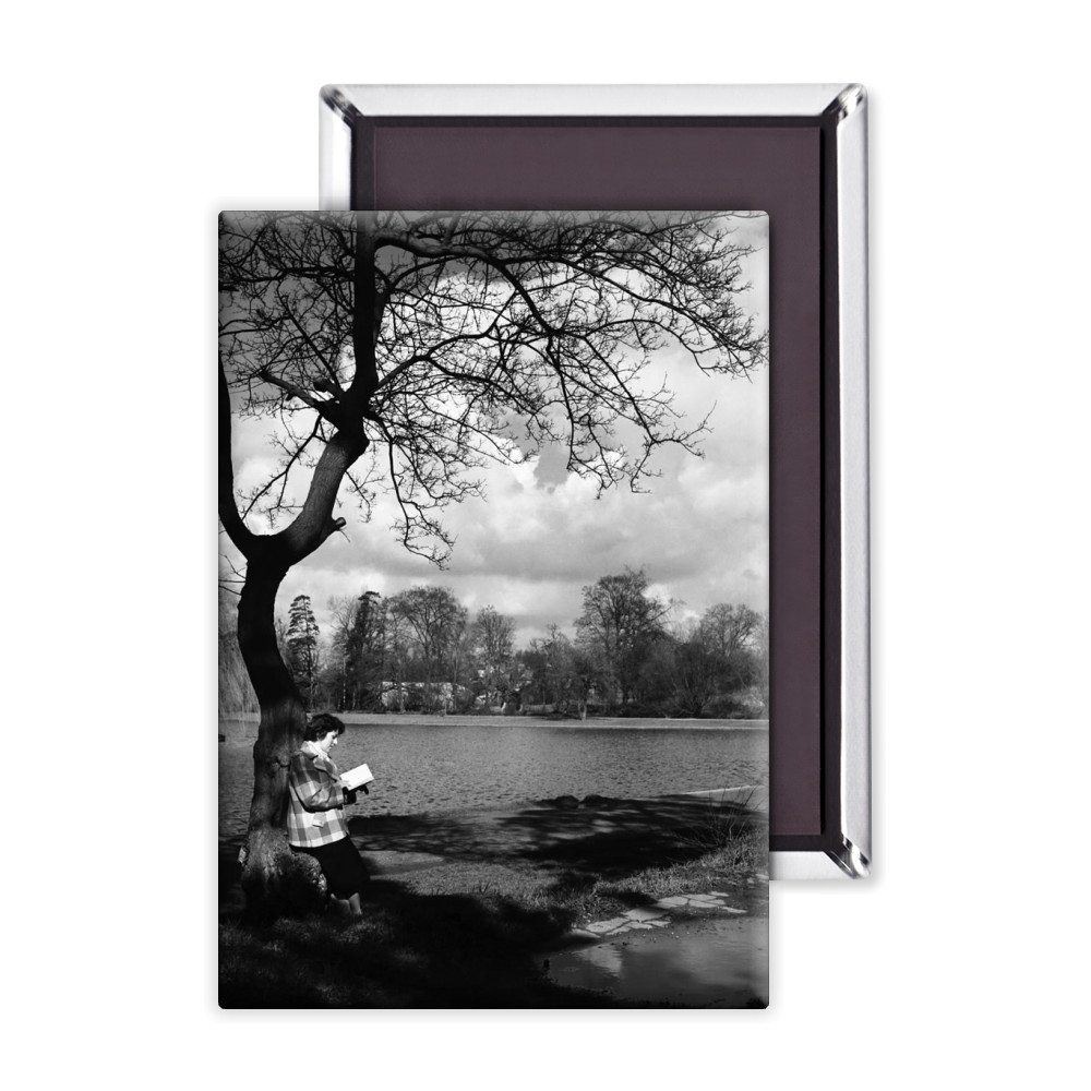 Woman reading her book by the lake in.. Magnet