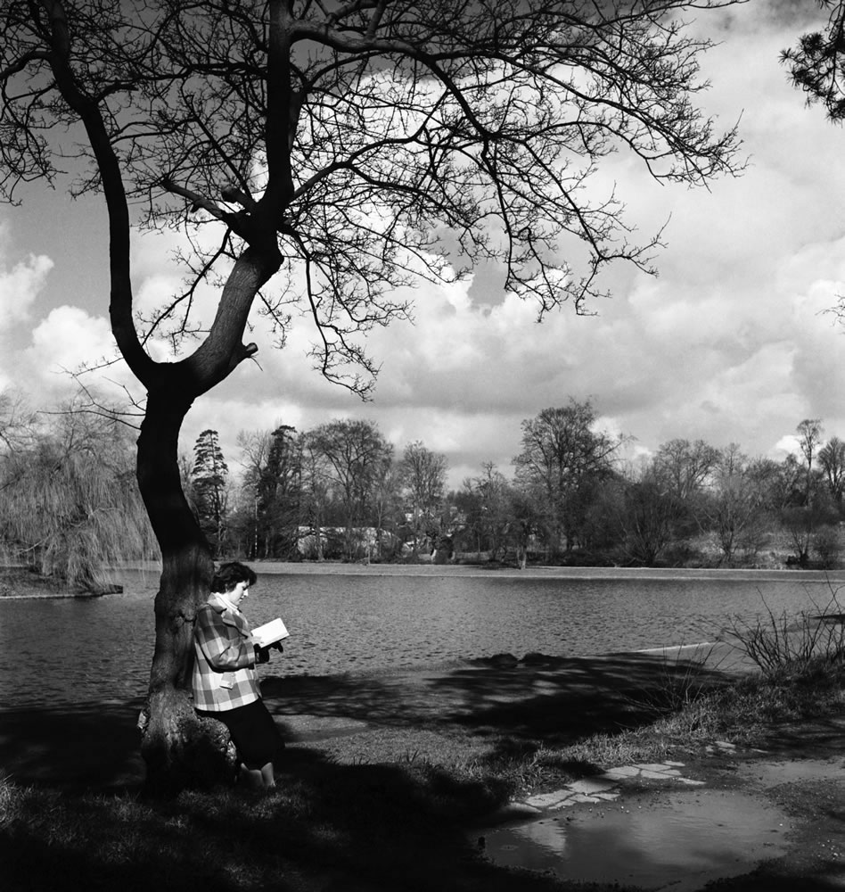 Woman reading her book by the lake in.. Art Print