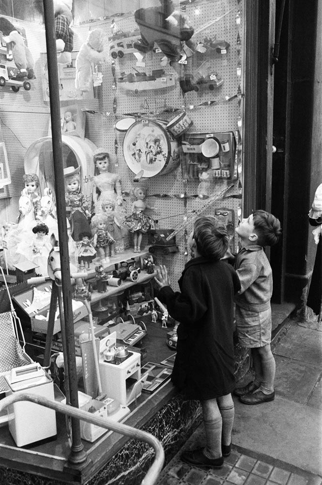 Children look longingly at toys into.. Art Print