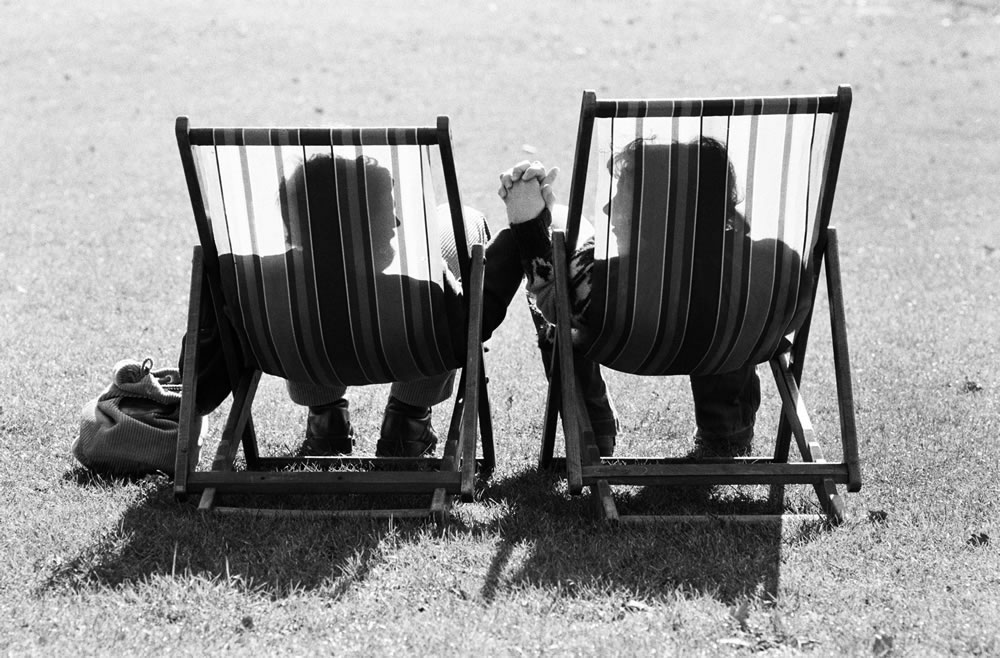 A couple in sit in a pair of deckchairs.. Art Print