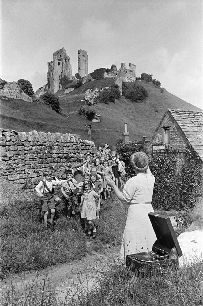A woman guides a group of children in.. Art Print