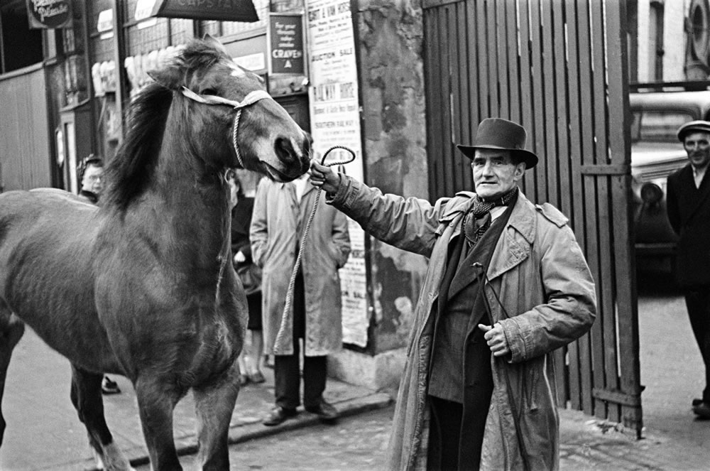 A man with a horse, standing outside.. Art Print