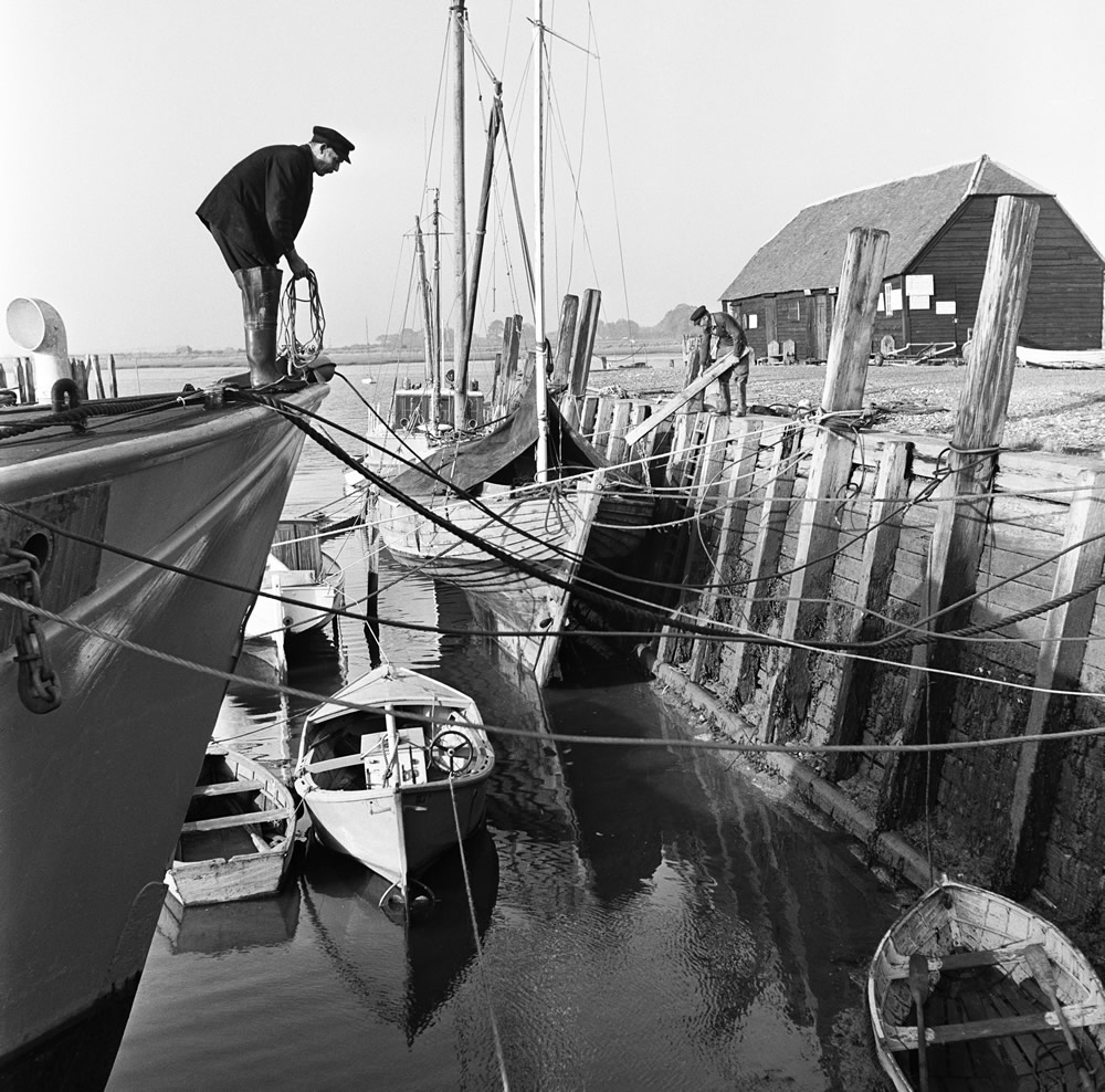 A fisherman mooring his boat at Bosham on the West Sussex Seafront. .. Art Print