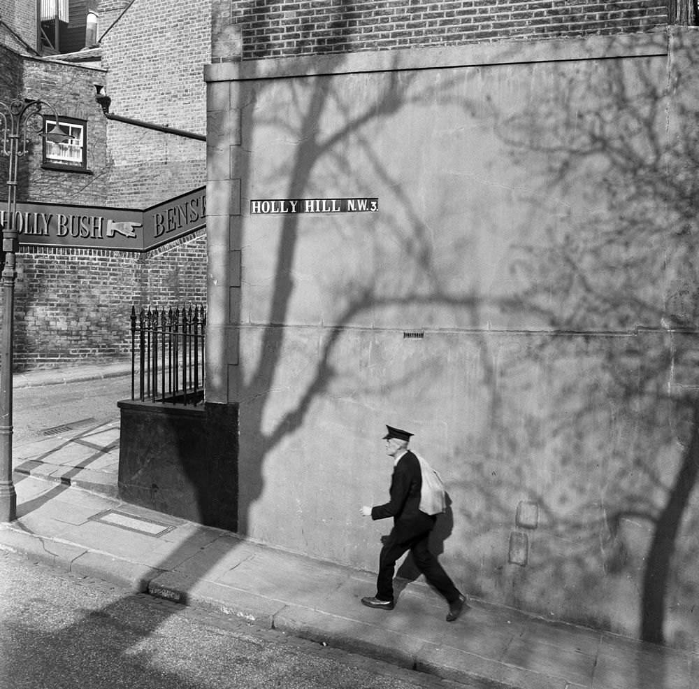 A postman walks along Holly Hill in Hampstead, North London. 8th April.. Art Print