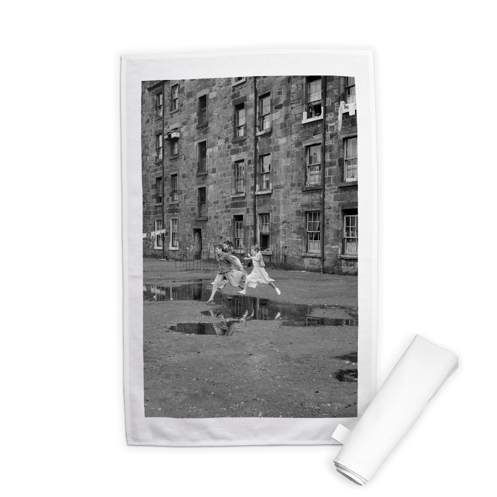 Three young friends leap over a puddle.. Tea Towel